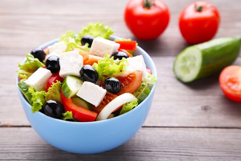Verse Griekse salade op kom met groenten op grijze houten achtergrond royalty-vrije stock foto