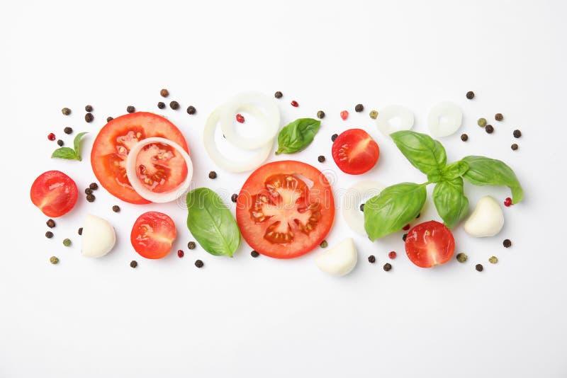 Verse groene basilicumbladeren, tomaten en mozarella op witte achtergrond stock afbeeldingen