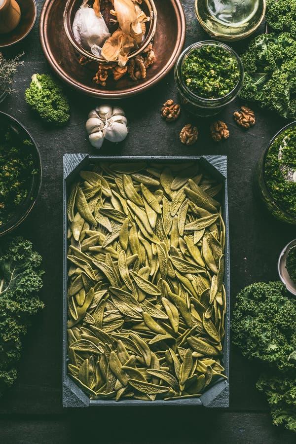 Verse groene deegwaren in houten dienblad op de donkere rustieke achtergrond van de keukenlijst met verse boerenkool en kokende i royalty-vrije stock foto