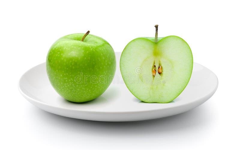 Verse groene die appel in een plaat op een witte achtergrond wordt geïsoleerd stock afbeelding