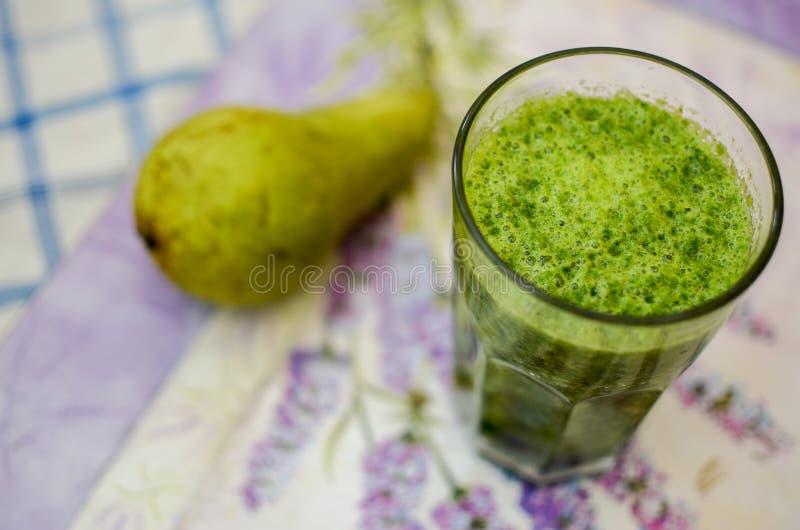 Verse groene die smoothie van peer en spinazie wordt gemaakt stock afbeeldingen