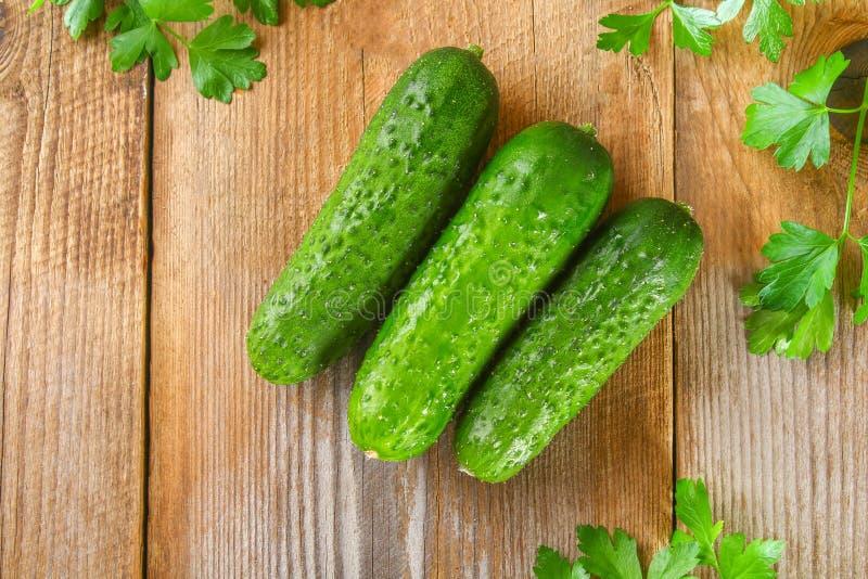 Verse groene eigengemaakte komkommer met peterselie op een oude houten lijst royalty-vrije stock foto's