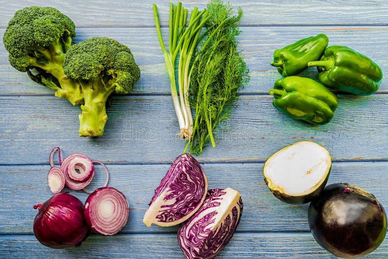 Verse groene en purpere groenten op blauwe houten achtergrond royalty-vrije stock fotografie
