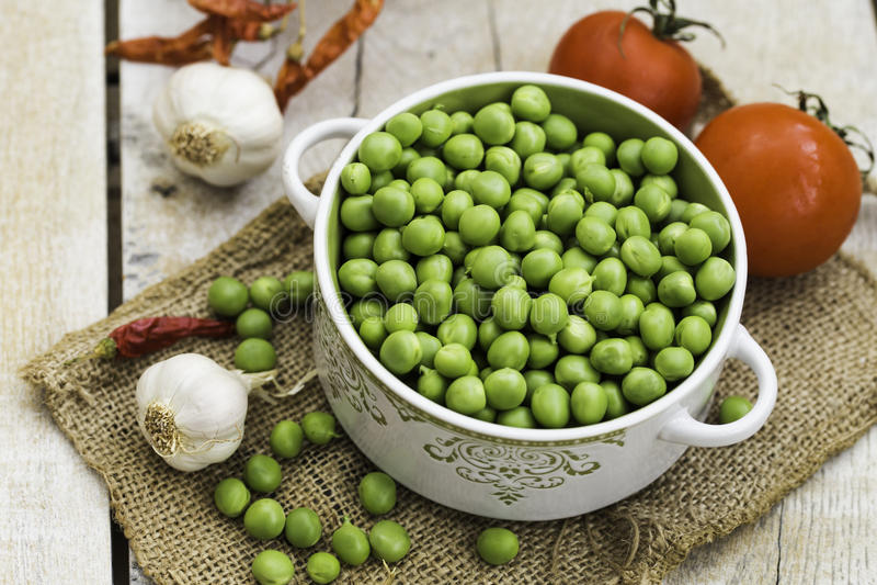 Verse groene erwten in een kom met tomaten, knoflook en Spaanse peper op de lijst stock foto's