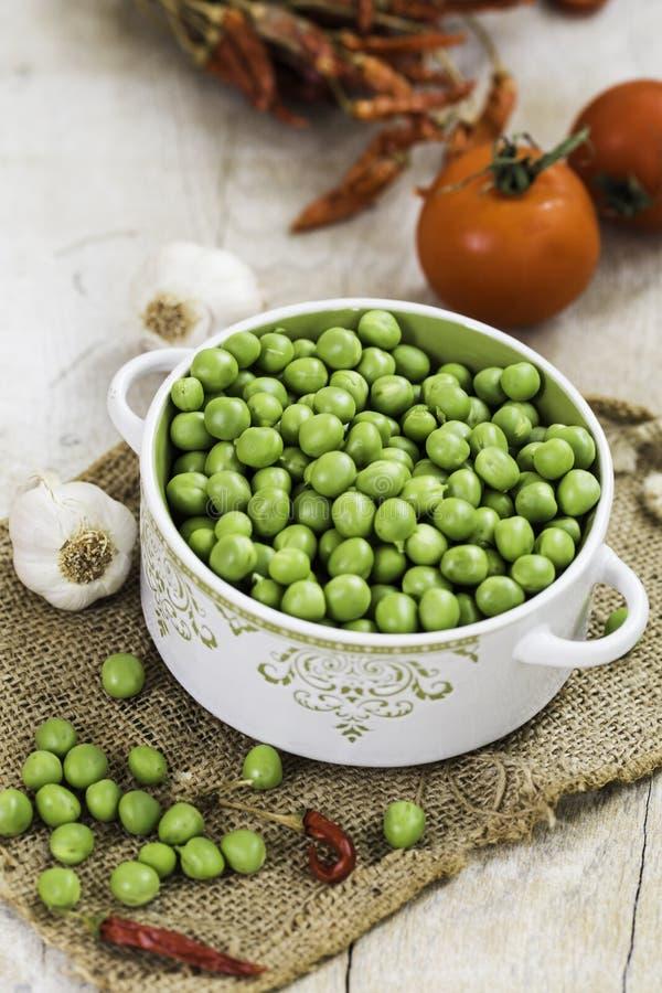 Verse groene erwten in een kom met tomaten, knoflook en Spaanse peper op de lijst royalty-vrije stock afbeeldingen