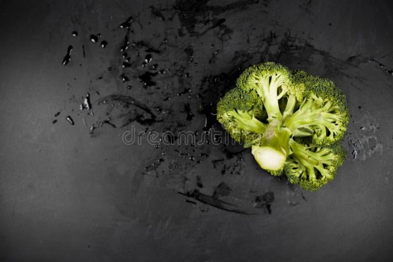 Verse groene natte broccoli op zwarte achtergrond stock afbeeldingen