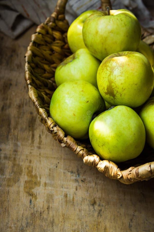 Verse groene organische ecologische appelen in rieten mand op rustieke houten lijst, hoogste mening, stilleven stock afbeelding