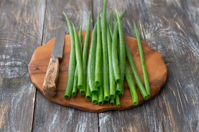 Verse groene organische uien en een mes op een houten oppervlakte stock afbeelding
