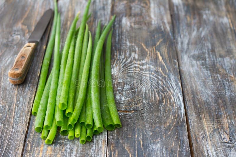 Verse groene organische uien en een mes op een houten oppervlakte royalty-vrije stock afbeelding