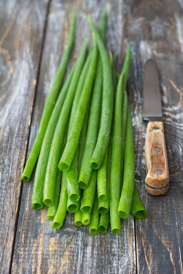 Verse groene organische uien en een mes op een houten oppervlakte royalty-vrije stock afbeeldingen