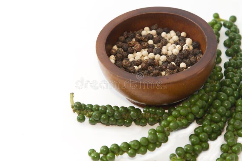 Verse groene paprika met hoop van zwart-witte peper in houten stock fotografie