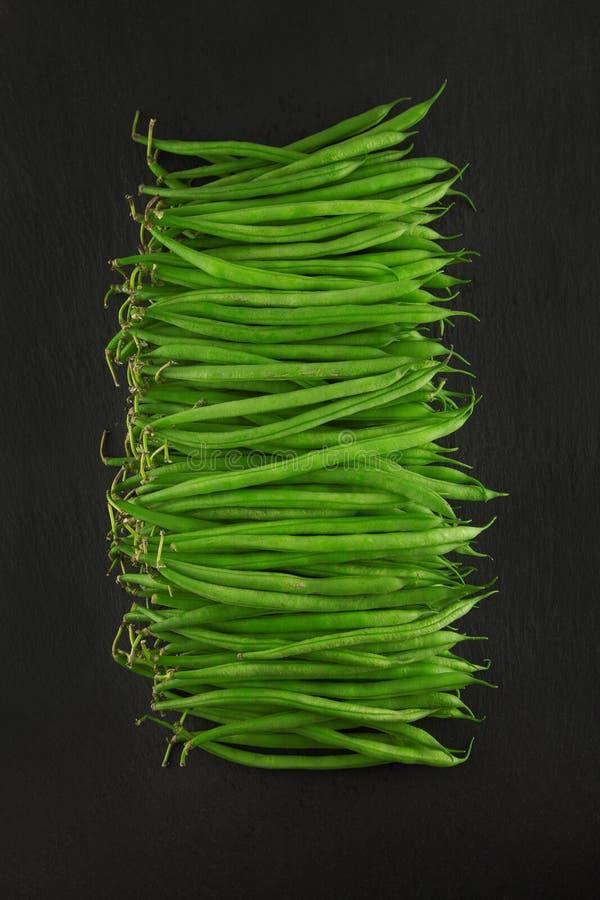 Verse groene prinsesbonen op de donkere plaat van de leikeuken, roestige sjofele elegant stock afbeelding