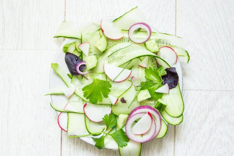 Verse groene salade met dun gesneden komkommer, radijs, rood ui en basilicum en jonge selderiebladeren op witte houten achtergron stock illustratie