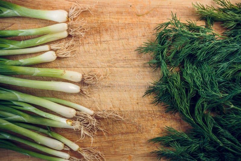 Verse groene uien en dille die op een houten scherpe Raad liggen stock fotografie