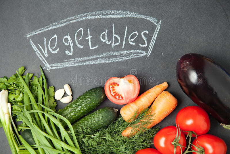 Verse groente op grafietraad met een inschrijving Hoogste mening ui, knoflook, peterselie, komkommer, aubergine, tomaat en dille royalty-vrije stock foto