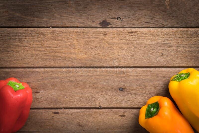Verse groente organische rode/oranje groene paprika's op houten backgr stock fotografie