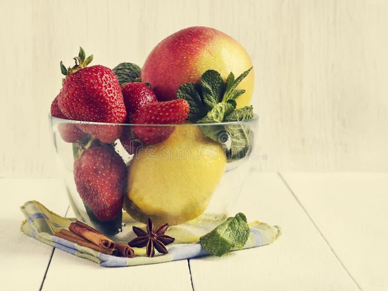 Verse groenten en vruchten in een glaskom Aardbei, appel, komkommer, citroen en munt royalty-vrije stock foto
