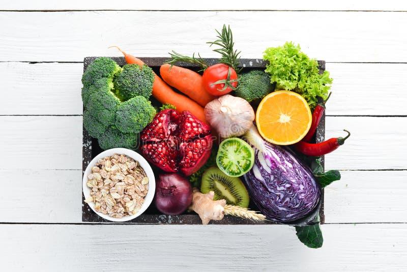 Verse groenten en vruchten in een houten doos op een witte houten achtergrond Zonnebloemzaden - zaadfonds stock afbeeldingen