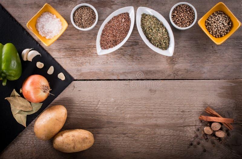 Verse groenten, Kruiden en kruiden in kommen Natuurlijke en bioingrediënten voor het koken op houten achtergrond royalty-vrije stock afbeeldingen
