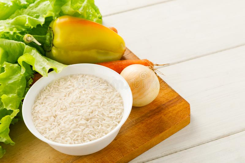 Verse groenten met rijst in een witte ceramische kom op een houten scherpe raad op een witte lijst stock foto