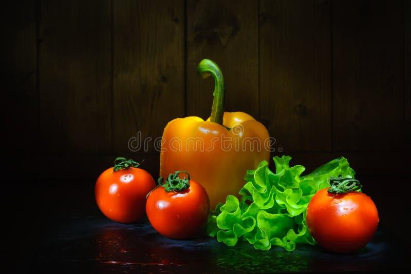 verse groenten na was op een lijst aangaande een houten achtergrond Donkere foto stock fotografie