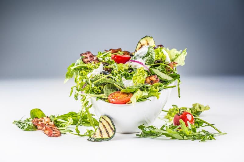 Verse groentesalade met de gebraden van de olijvenarugula van bacontomaten vulling van de courgettetzatziki en olijfolie stock afbeelding