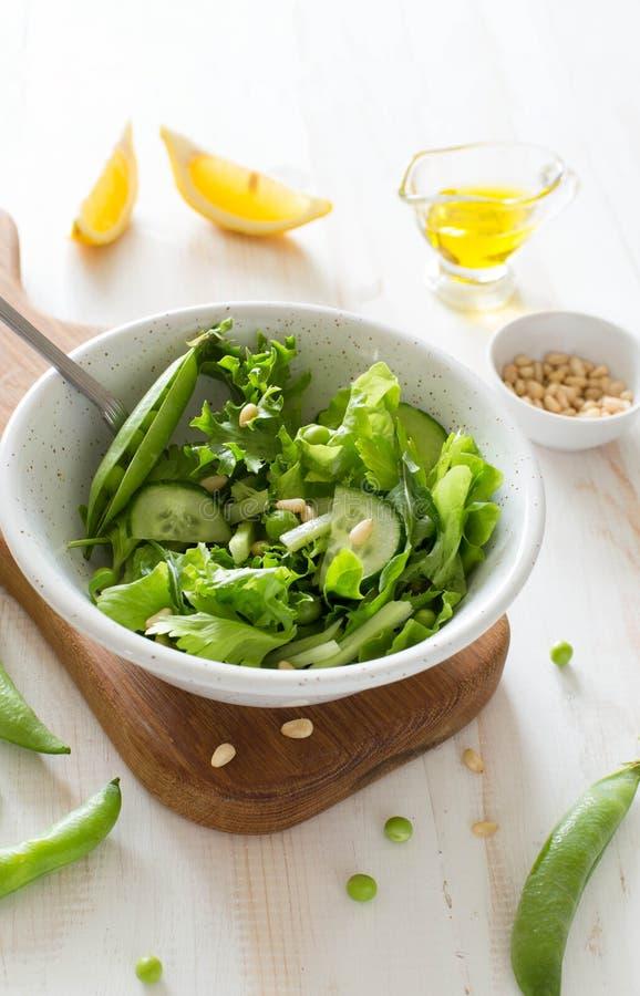 Verse groentesalade met greens, komkommer, erwten en pijnboomnoten stock foto