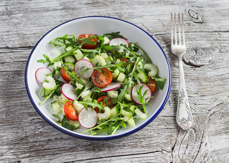 Verse groentesalade met kersentomaten, komkommers, radijzen en arugula Gezond vegetarisch voedsel stock afbeelding