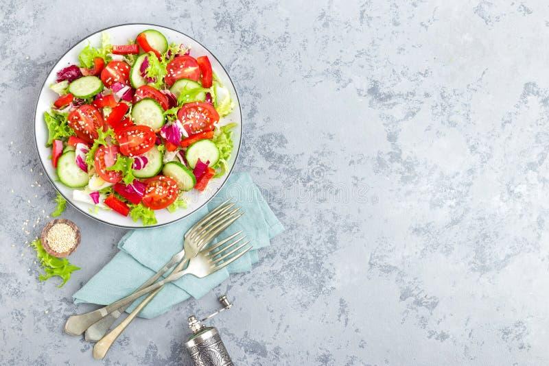 Verse groentesalade met tomaten, komkommers, paprika en sesamzaden Plantaardige salade op witte plaat royalty-vrije stock afbeeldingen