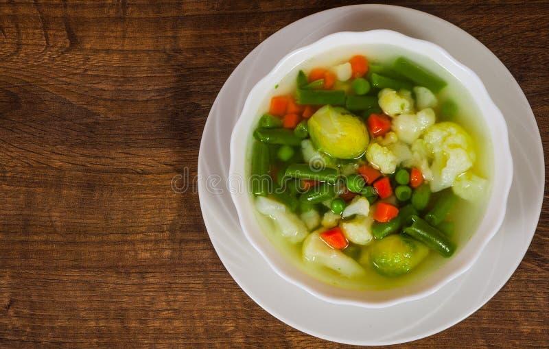 Verse groentesoep in kom op houten lijst met exemplaarruimte stock fotografie