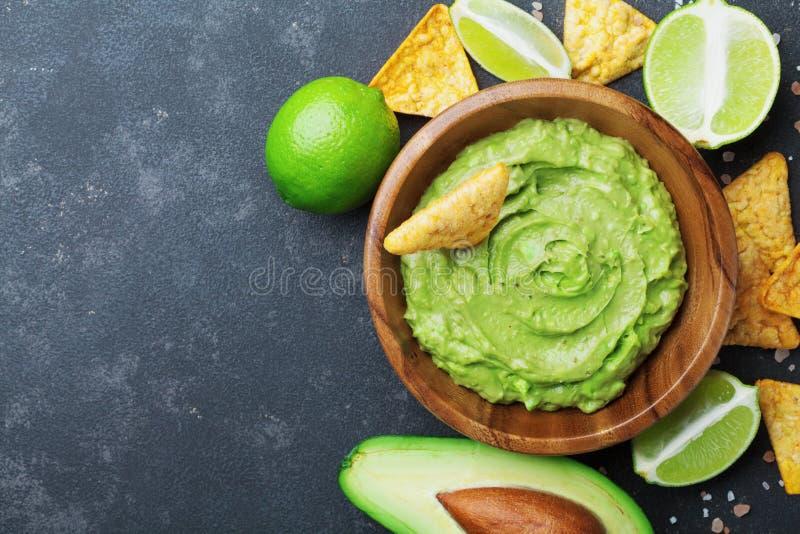 Verse guacamoleonderdompeling met avocado, kalk en nachos op de zwarte mening van de lijstbovenkant De ruimte van het exemplaar T royalty-vrije stock foto's