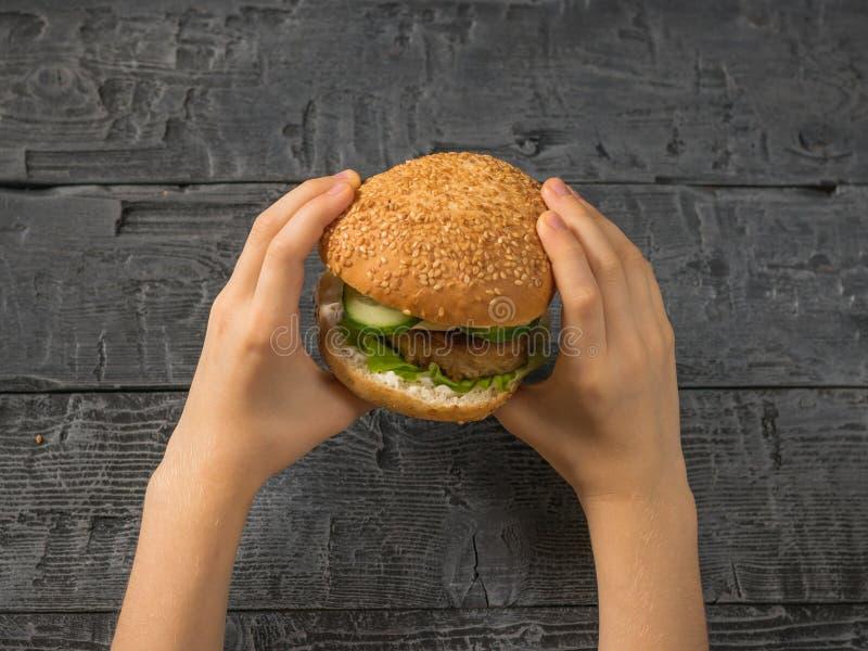 Verse hamburger in de handen van een kind over de lijst Eigengemaakt voedsel Rustieke stijl royalty-vrije stock afbeelding