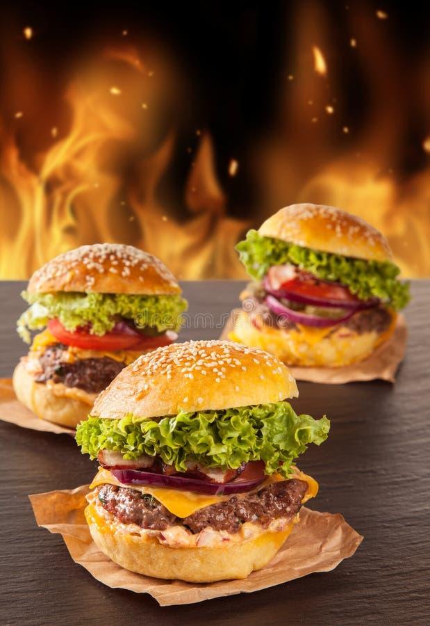 Verse hamburgers met brandvlammen stock fotografie