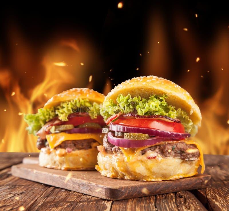 Verse hamburgers met brandvlammen royalty-vrije stock afbeelding