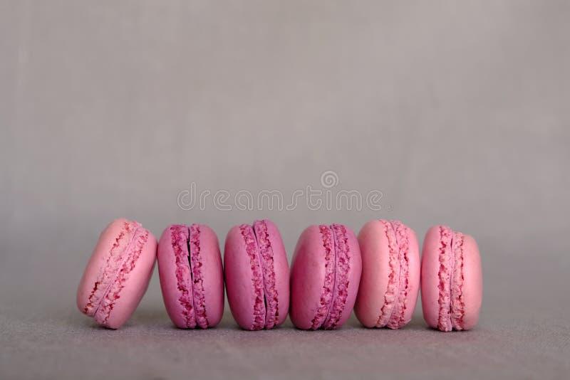 Verse heerlijke roze en purpere Franse macarons op grijze achtergrond Ruimte voor tekst Kleurrijke schuimgebakje gebaseerde koekj stock afbeeldingen
