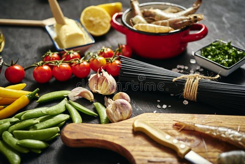 Verse heerlijke ruwe tijgergarnalen in een pot met peterselie, citroen, boter, tomaten en Spaanse peperpeper stock afbeelding