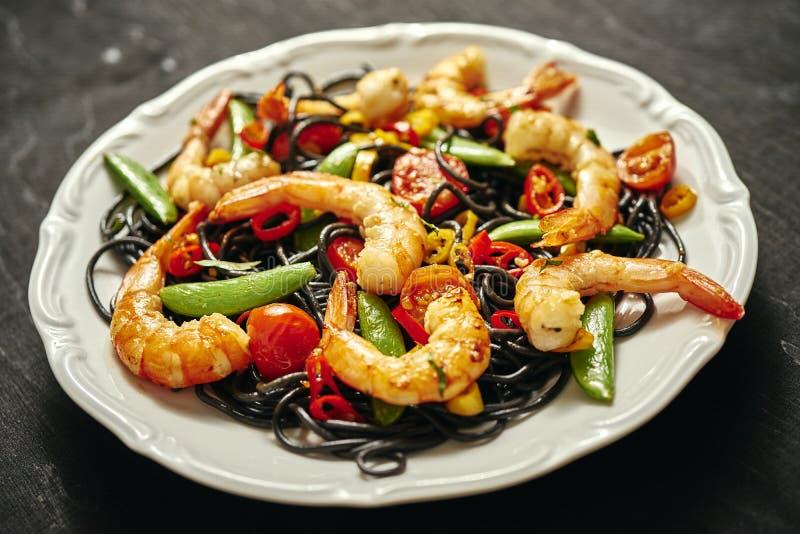 Verse, heerlijke zwarte spaghetti met geroosterde garnalen, tomaten, Spaanse pepers, op een witte plaat stock afbeelding