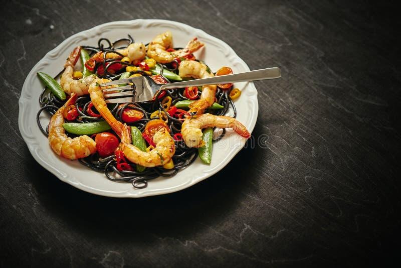 Verse, heerlijke zwarte spaghetti met geroosterde garnalen, tomaten, Spaanse pepers, op een witte plaat stock foto