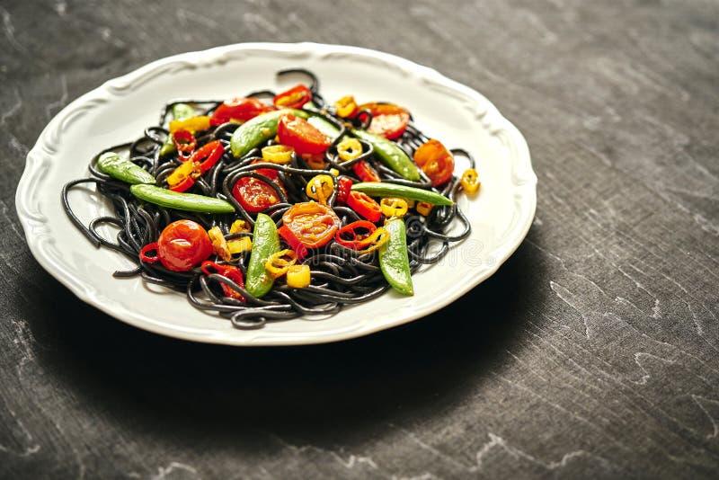 Verse heerlijke zwarte veganistspaghetti met tomaten, Spaanse peperpeper, op een witte plaat royalty-vrije stock afbeelding