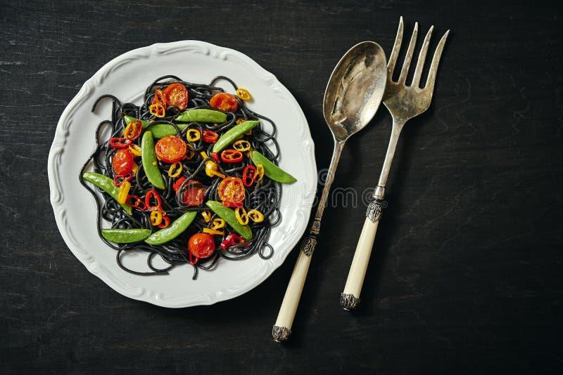 Verse heerlijke zwarte veganistspaghetti met tomaten, Spaanse peperpeper, op een witte plaat royalty-vrije stock foto's