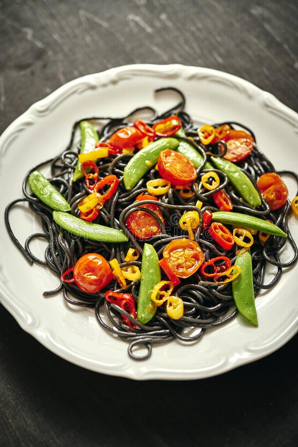 Verse heerlijke zwarte veganistspaghetti met tomaten, Spaanse peperpeper, op een witte plaat royalty-vrije stock fotografie