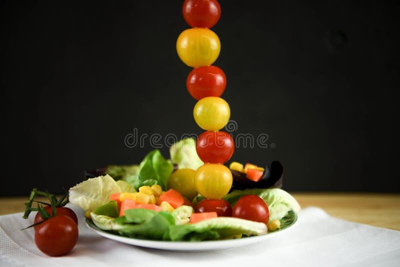 Verse heldere de zomersalade op een plaat met minitomaten in een lange verticale lijn stock foto
