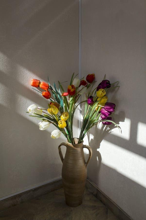 Verse heldere witte, gele, rode en purpere tulpen in een uitstekende vaas met handvatten in een hoek in een strook van licht en s royalty-vrije stock foto