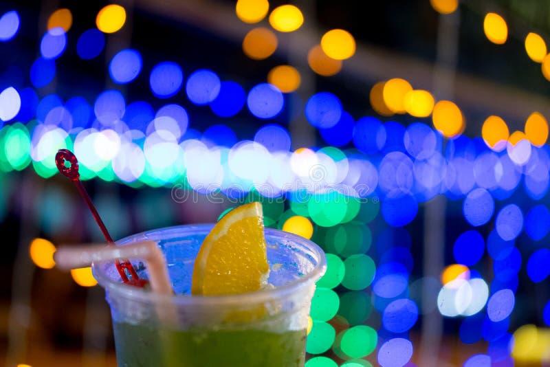 Verse het fruitcocktail van de sapmengeling in plastic glas op bokeh feestelijke achtergrond royalty-vrije stock afbeeldingen