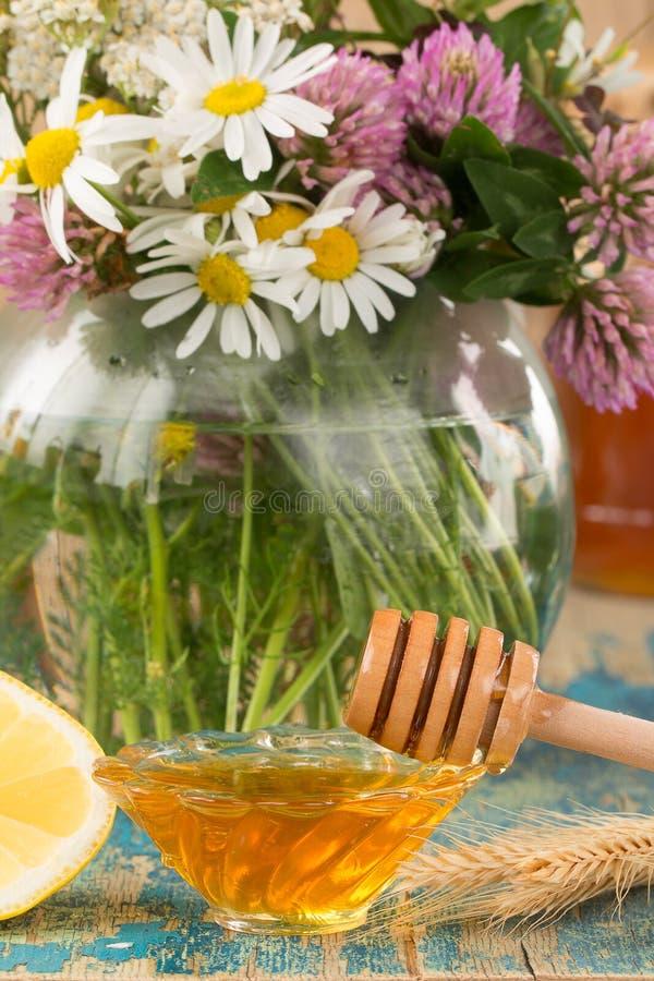 Verse honing en bloemen op de lijst stock afbeeldingen