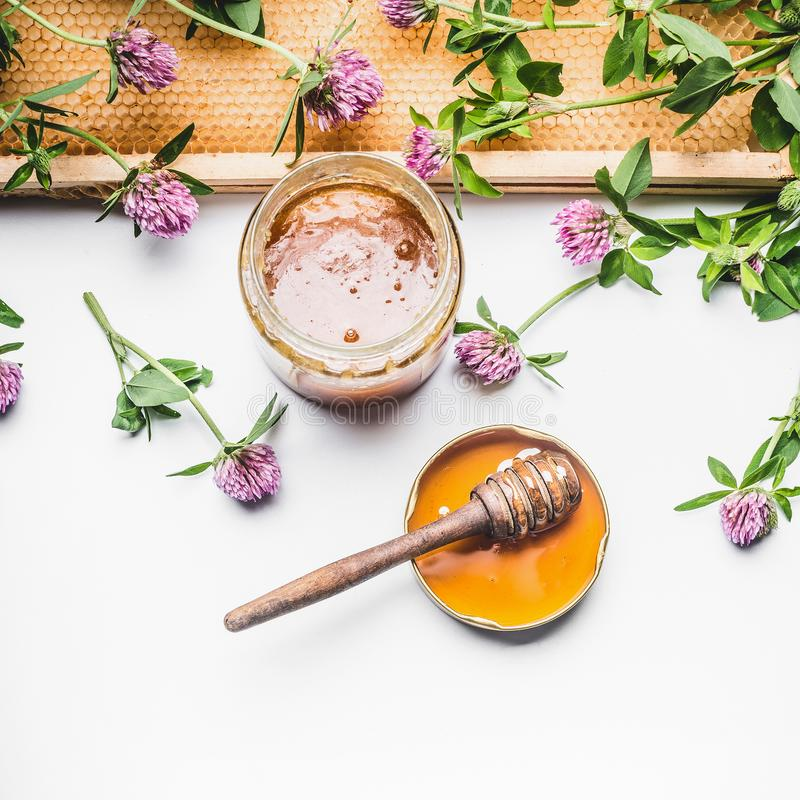 Verse honing in glaskruik met honingslepel, honingskam en wilde bloemen op witte achtergrond royalty-vrije stock afbeelding