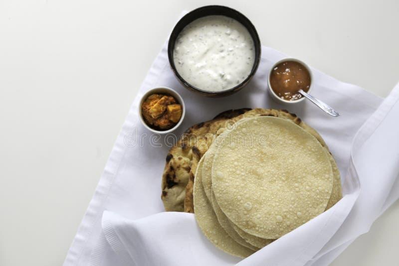 Verse Indische vlakke broden Naans en poppadums gediend op de witte doek royalty-vrije stock fotografie