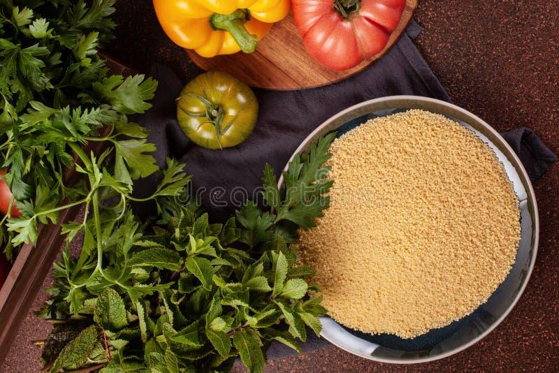 Verse ingrediënten voor tabboulehsalade: kouskous, tomaten, citroen, peterselie, munt, olijfolie, groene paprika royalty-vrije stock fotografie