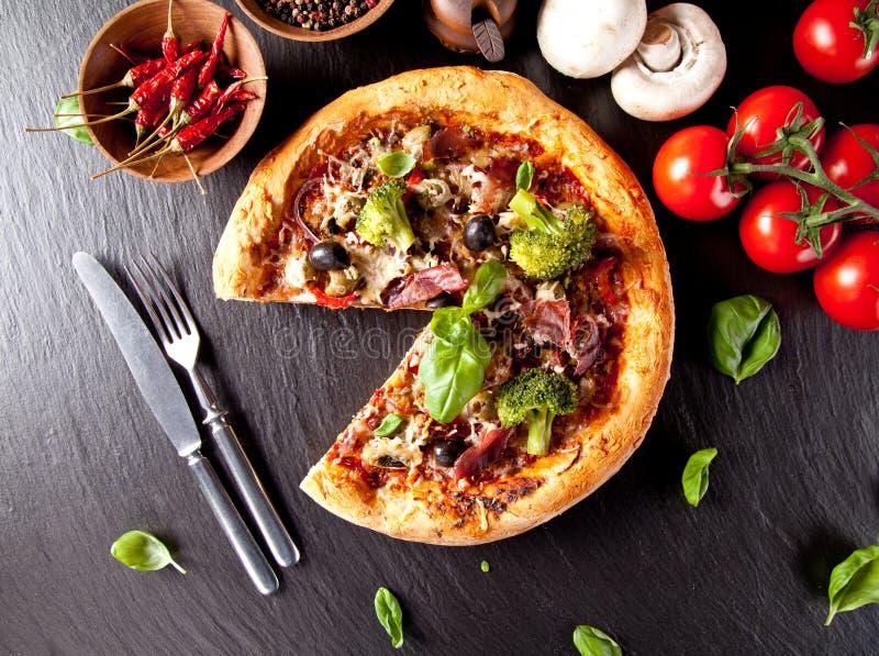 Verse Italiaanse die pizza op zwarte steen wordt gediend royalty-vrije stock afbeeldingen