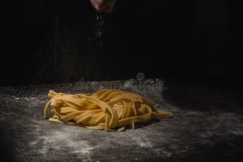 Verse Italiaanse ongekookte eigengemaakte deegwaren Handen die deegwaren maken spaghetti Verse Italiaanse spaghetti Close-up van  royalty-vrije stock afbeeldingen